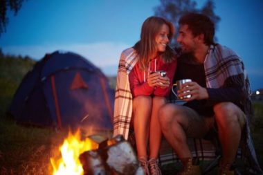 Couple sitting by camp fire