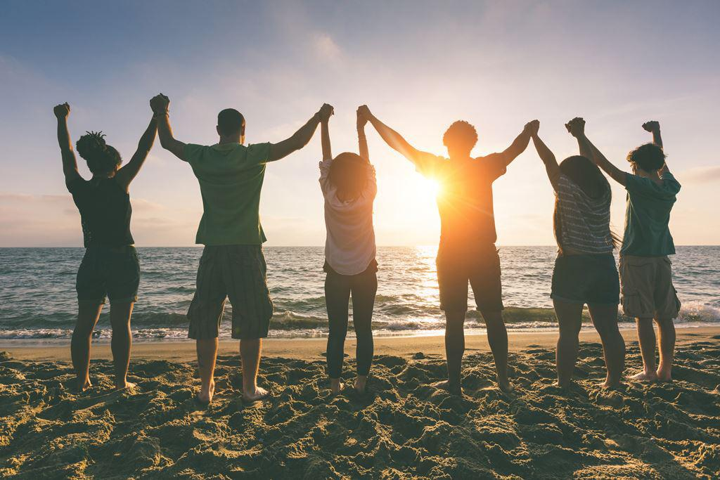 Group of people holding raised arms on beach