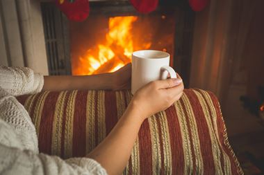 Woman with hot drink by cosy fire